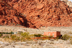 Red Adobe Home in Desert by Mountains Royalty Free Stock Photo