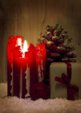 Red Advent candle  and gift. Royalty Free Stock Photo