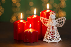 Red advent candles on the old wooden background with christmas light curtain Royalty Free Stock Photo