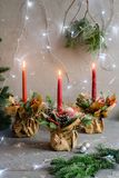 Red advent flower arrangement with three burning candles royalty free stock photos