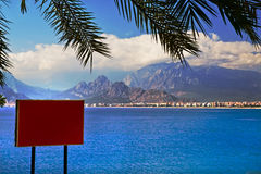 Red advertisment board on sea shore. Bright red information board at sea shore with  mountains in background Stock Photography