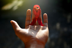 Red aids ribbon in hand. Royalty Free Stock Image
