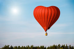 Red air balloon in the shape of a heart flying in blue sky Royalty Free Stock Images