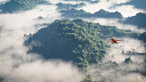 Red airplane flying over mountains with pine trees in the clouds. Royalty Free Stock Photos