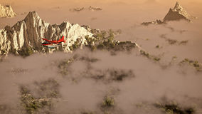 Red airplane flying over snow mountains with pine trees in the clouds. Stock Images
