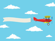 Red airplane with pilot and advertising banner in the cloudy sky Stock Images
