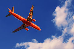 Red airplane in the sky at sunset with landing lights on. Red airplane in the sky at sunset with landing lights stock photo