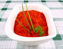 Red ajvar in white bowl with parsley, spring onion Royalty Free Stock Images