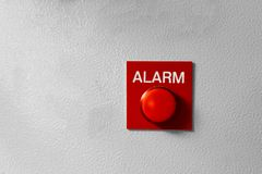 Red Alarm button signal on the painted grey wall. Concept of any alarm situation - fire, bankrupt, robbery etc royalty free stock photos