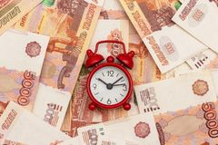 Red alarm clock on the background of Russian five thousandth bills. Concept Time is money.  stock images