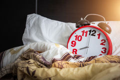 Red Alarm Clock On The Bed Stock Photo