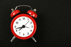 Red alarm clock on black chalkboard Royalty Free Stock Photography