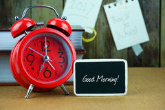 Red alarm clock and blackboard on wooden table. Stock Image