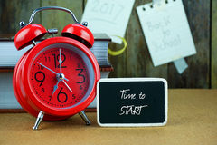 Red alarm clock and blackboard on wooden table. Stock Photo