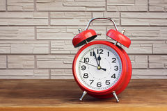 Red alarm clock on brick wall background Royalty Free Stock Image