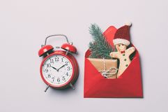 Red alarm clock and Christmas gifts in envelope Royalty Free Stock Image