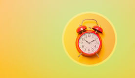 Red alarm clock in cirlce. On colored background Stock Photo