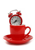 Red alarm clock in coffee cup over white Stock Images