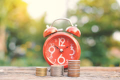 Red alarm clock with coin on old wood Stock Photo