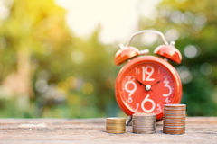 Red alarm clock with coin on old wood Royalty Free Stock Photos