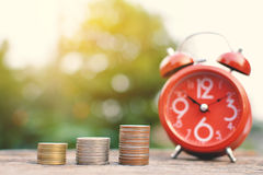 Red alarm clock with coin on old wood Royalty Free Stock Images