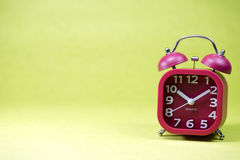 Red alarm clock on a green background Stock Images