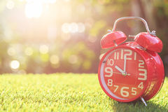 Red alarm clock on green grass with sunlight blur and bokeh back Royalty Free Stock Images