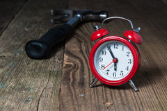 Red alarm clock and hammer on the wooden table Royalty Free Stock Photography