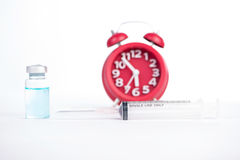 Red alarm clock and injection vials background Stock Images