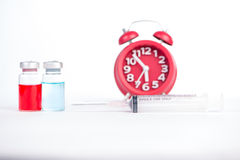 Red alarm clock and injection vials background Royalty Free Stock Photos