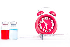 Red alarm clock and injection vials background Royalty Free Stock Images