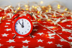 Red alarm clock with lights bokeh on a red fabric background wit Royalty Free Stock Image