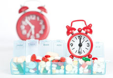 Red alarm clock and medicine in weekly pill box Stock Photos