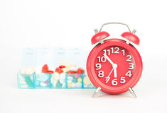 Red alarm clock and medicine in weekly pill box Royalty Free Stock Photos