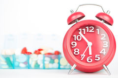 Red alarm clock and medicine in weekly pill box Stock Image
