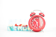 Red alarm clock and medicine in weekly pill box Royalty Free Stock Photo