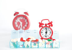 Red alarm clock and medicine in weekly pill box Stock Images