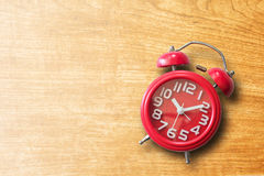 Red alarm clock on old brown wooden plank background. Royalty Free Stock Photo