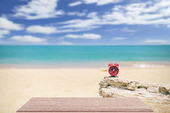 Red alarm clock on old wood with sea beach background, summer ti Stock Photos