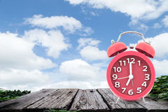 Red  alarm clock on a old wooden ,on blue sky background Stock Images
