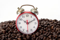 Red alarm clock over coffee beans. Red alarm clock over coffee beans on white background Stock Photo