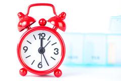 Red alarm clock and pill box background show medicine time Stock Photo