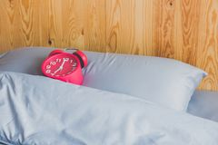 Red alarm clock on pillow on rustic bed. Red alarm clock on pillow on rustic bed Royalty Free Stock Photography