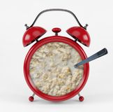 Red alarm clock with porridge concept isolated on white background Stock Photo