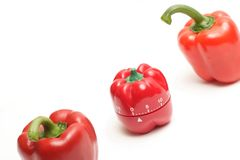 Red alarm clock and red peppers Stock Image