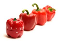 Red alarm clock and red peppers Royalty Free Stock Photo