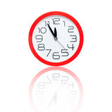 Red alarm clock showing five minutes to midnight with reflection Stock Images