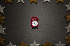 Red alarm clock on slate with star frame Royalty Free Stock Photo