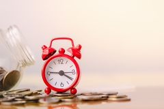 Red alarm clock on stack of coins in concept of savings and money growing or energy save. Business investment growth concept. royalty free stock photos