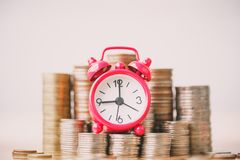 Red alarm clock on stack of coins in concept of savings and money growing or energy save. royalty free stock images